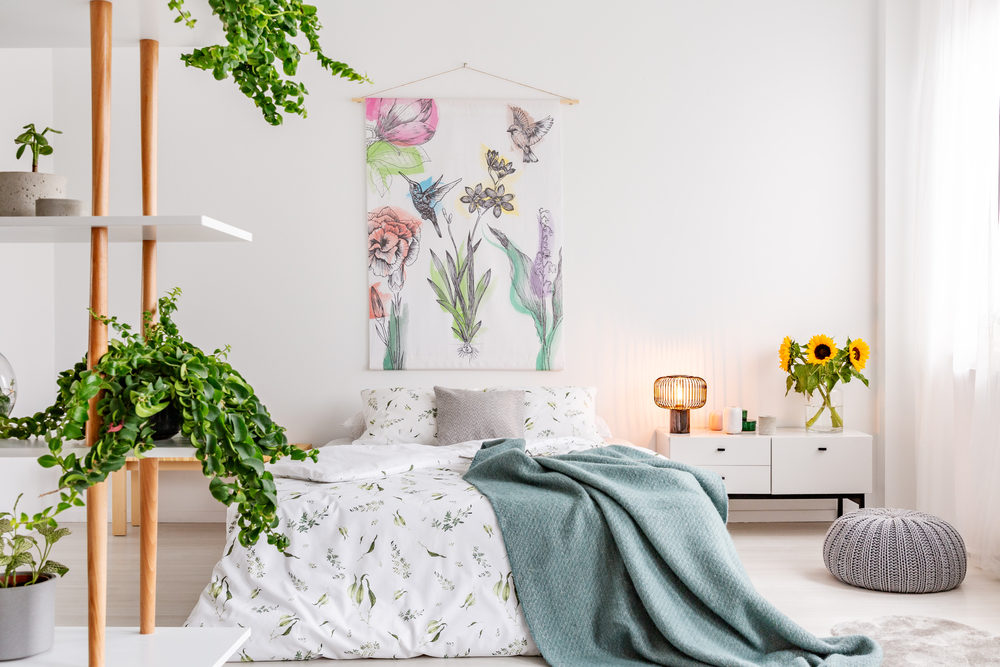 green-plants-on-shelves-beside-a-bed-dressed-in-white-cotton-bedding-and-teal-blue-blanket-in-a-bright-bedroom-interior-flowers-and-birds-painted-on-the-fabric-above-the-bed-real-photo