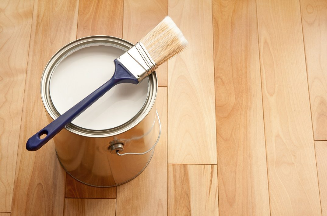 paintbrush-and-a-can-of-white-paint-on-wooden-floor