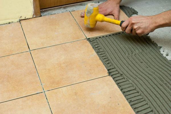 Простукивание уложенной плиткой для лучшего схватывания с цементом
