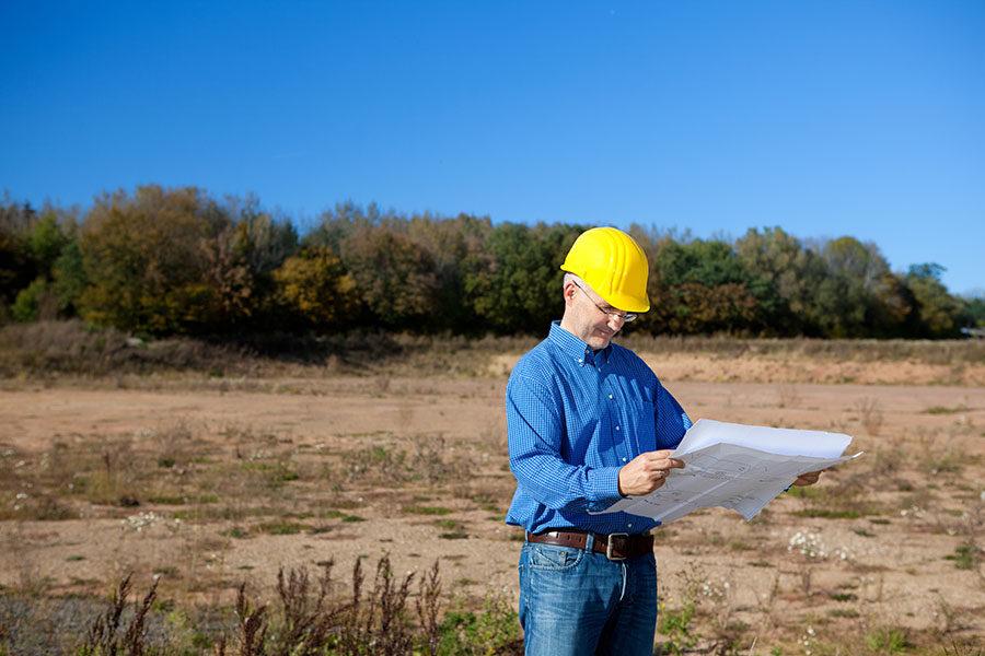 architect-holding-blueprint-on-construction-site