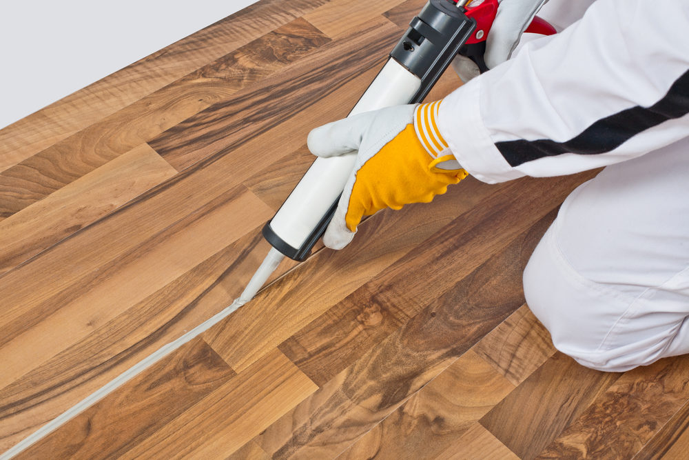 worker-applies-silicone-sealant-spaces-of-old-wooden-floor