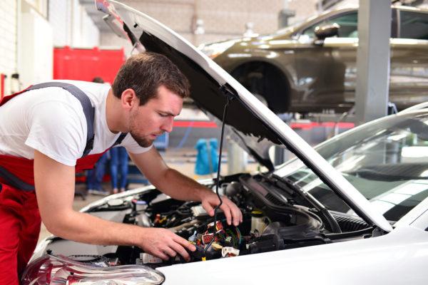 automechaniker-in-einer-werkstatt-repariert-fahrzeug