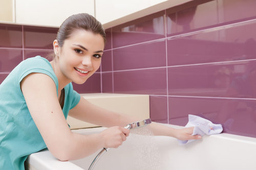 smiling-woman-cleaning-bathroom